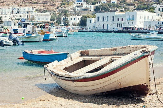 White and Maroon Jon Boat on Seashore