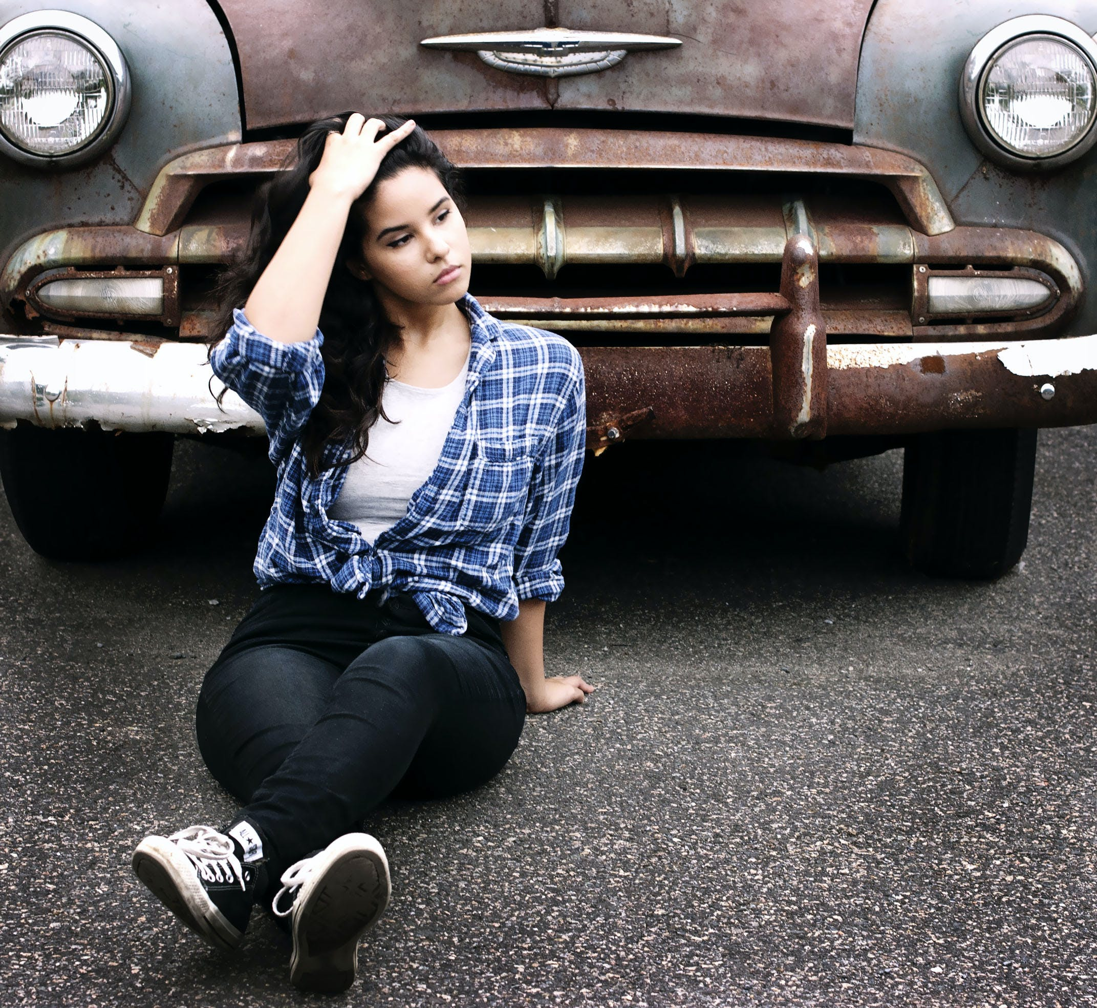 Woman in Blue Sports Shirt Sitting Infront of Vintage Brown Car
