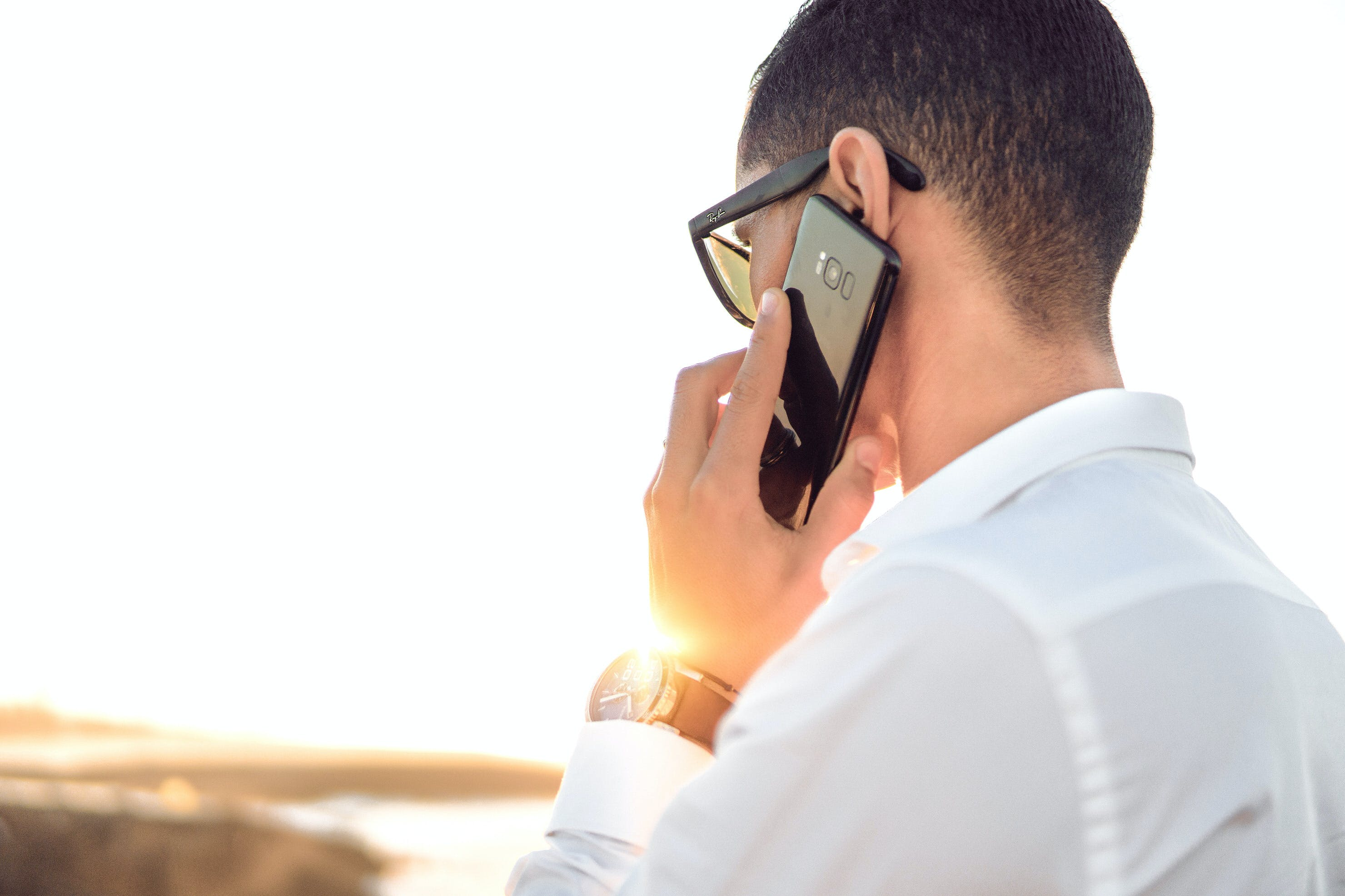 Shallow Focus Photography of a Man in White Collared Dress Shirt Talking to the Phone Using Black Android Smartphone