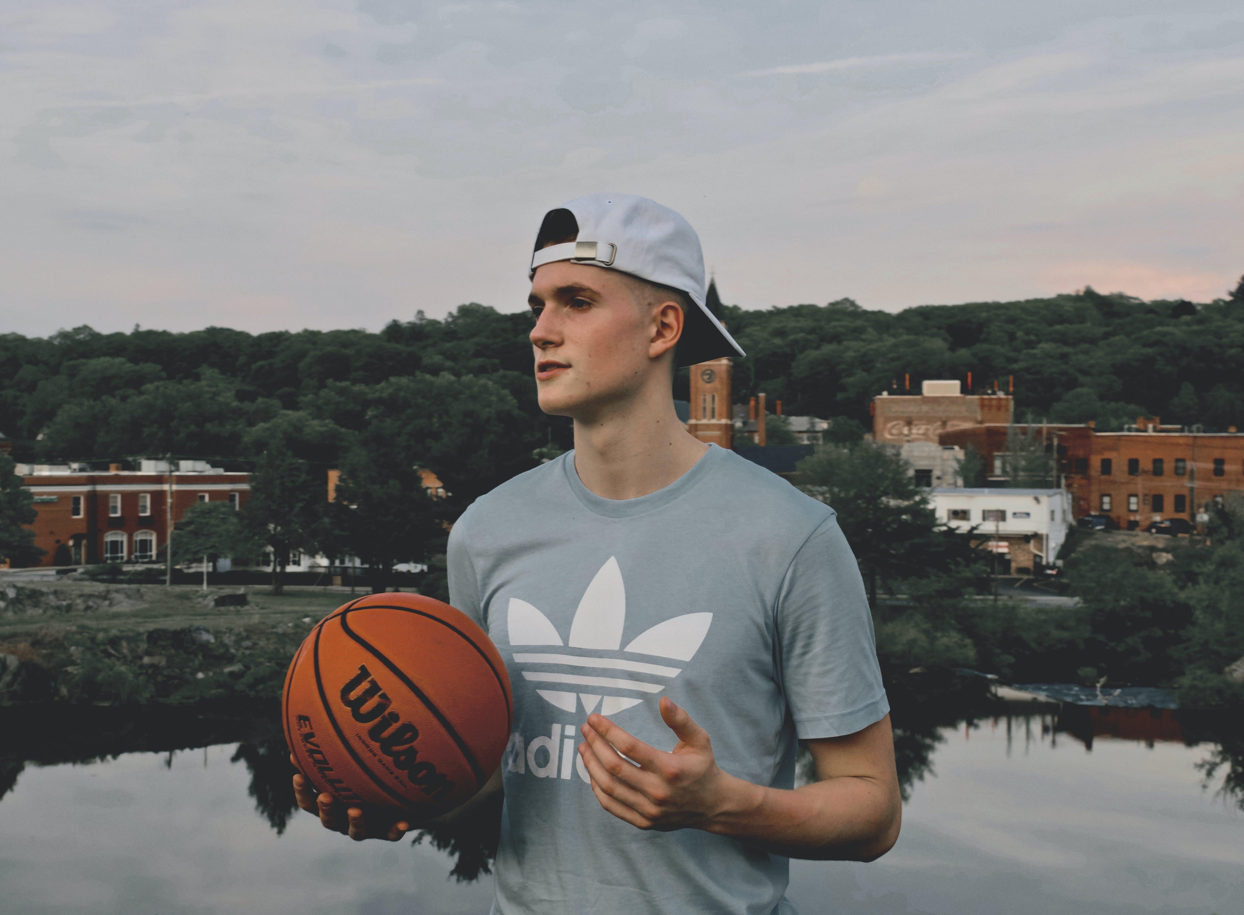 Man Wearing Gray Crew Neck Shirt Holding Basketball