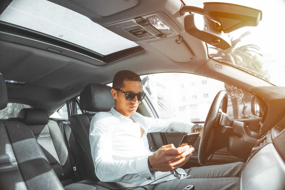 Inside the car, a man holds his smartphone. | Photo: Pexels
