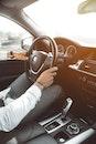 Man in White Dress Shirt Holding Steering Wheel
