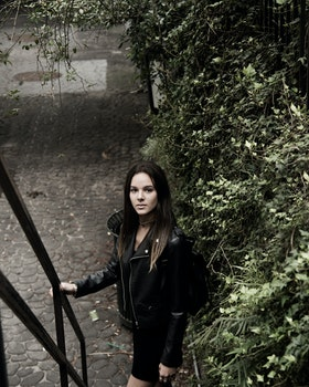 Close Up Photograph of Woman With Black Leather Jacket Standing Beside Stair Handle