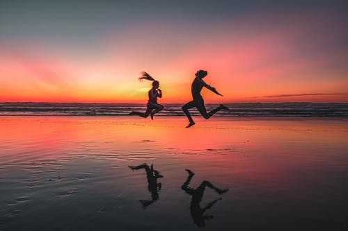 Silhouette of Man and Woman Jumping on Beach during Sunset
