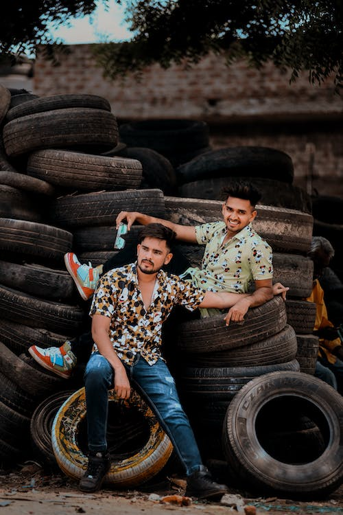 Two Male Models Sitting on Pile of Tires