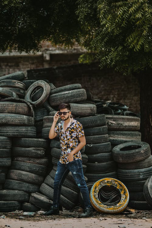 Male Model Standing near the Pile of Tires