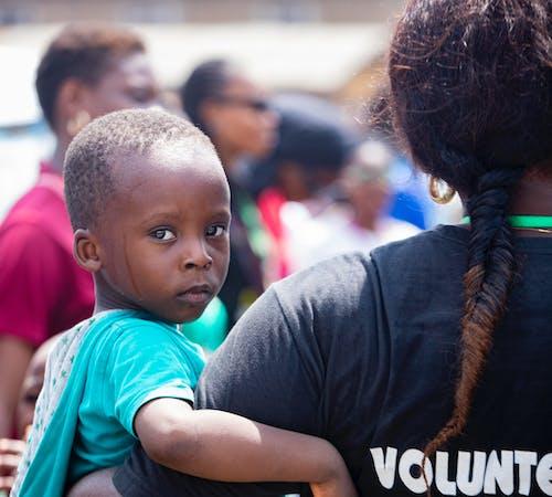 Volunteer Woman Carrying a Boy