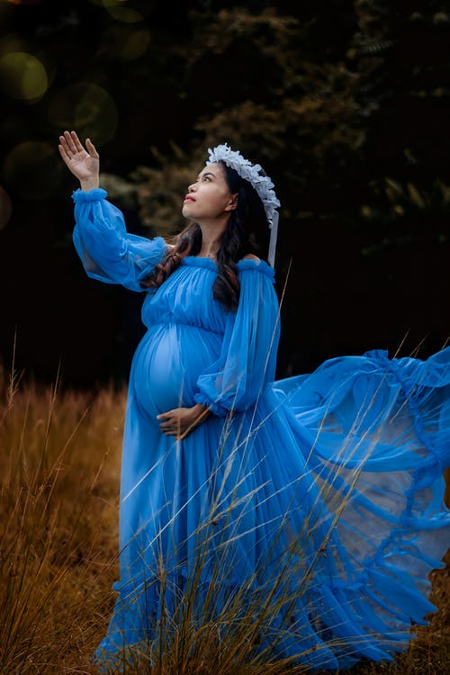 Stylish pregnant woman standing with raised arm and touching belly in nature