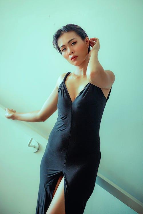 Stylish Asian woman in black dress standing near wall