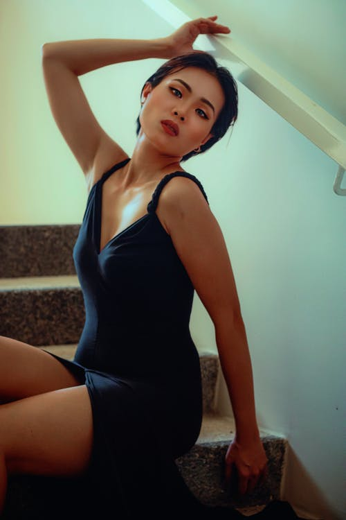 Calm Asian female with dark hair in black dress sitting on stairs and looking at camera against light wall