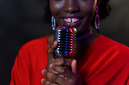 Close-Up Photo of Woman Singing while Holding Her Microphone