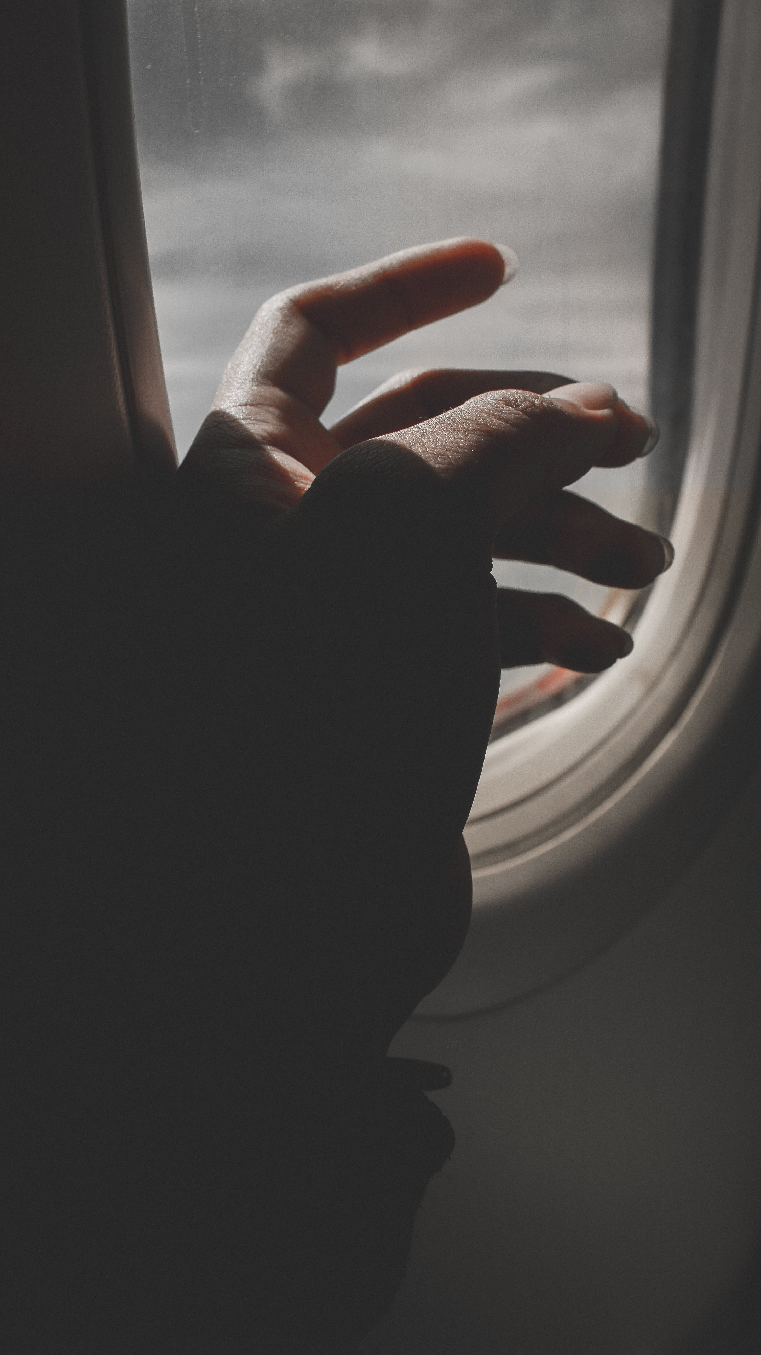 Hand By Airplane Window