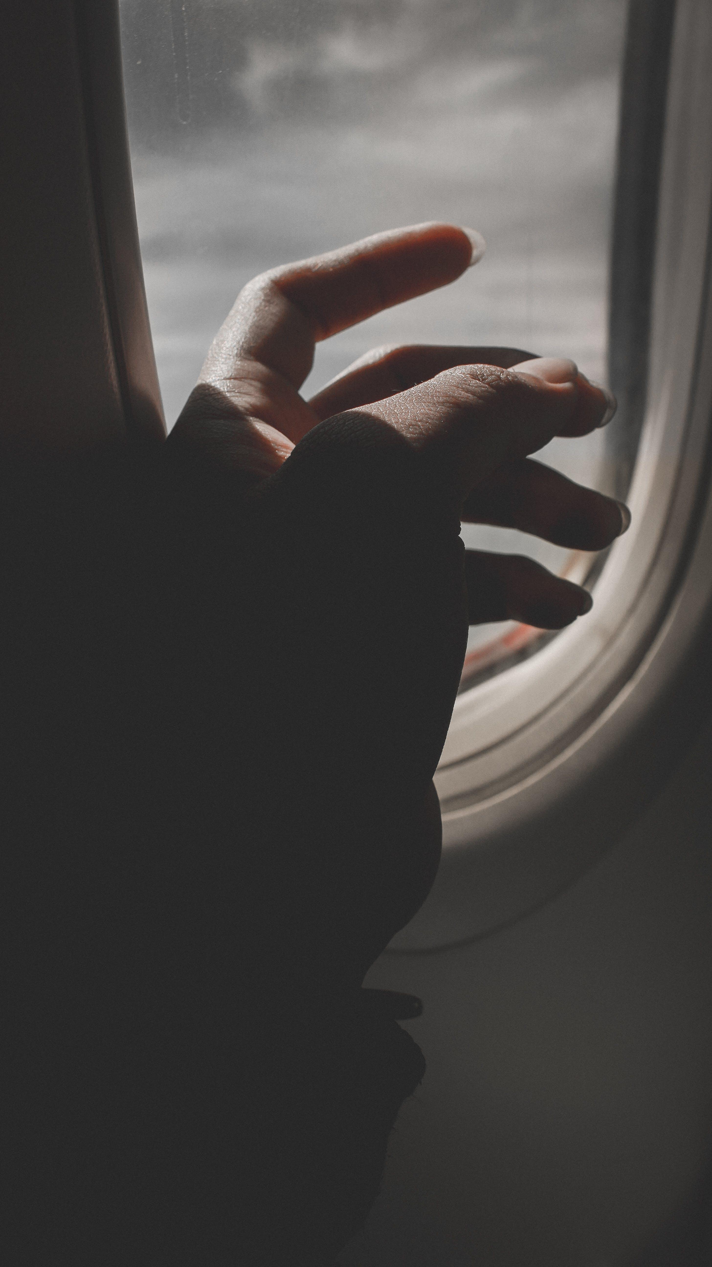 Hand By Airplane Window