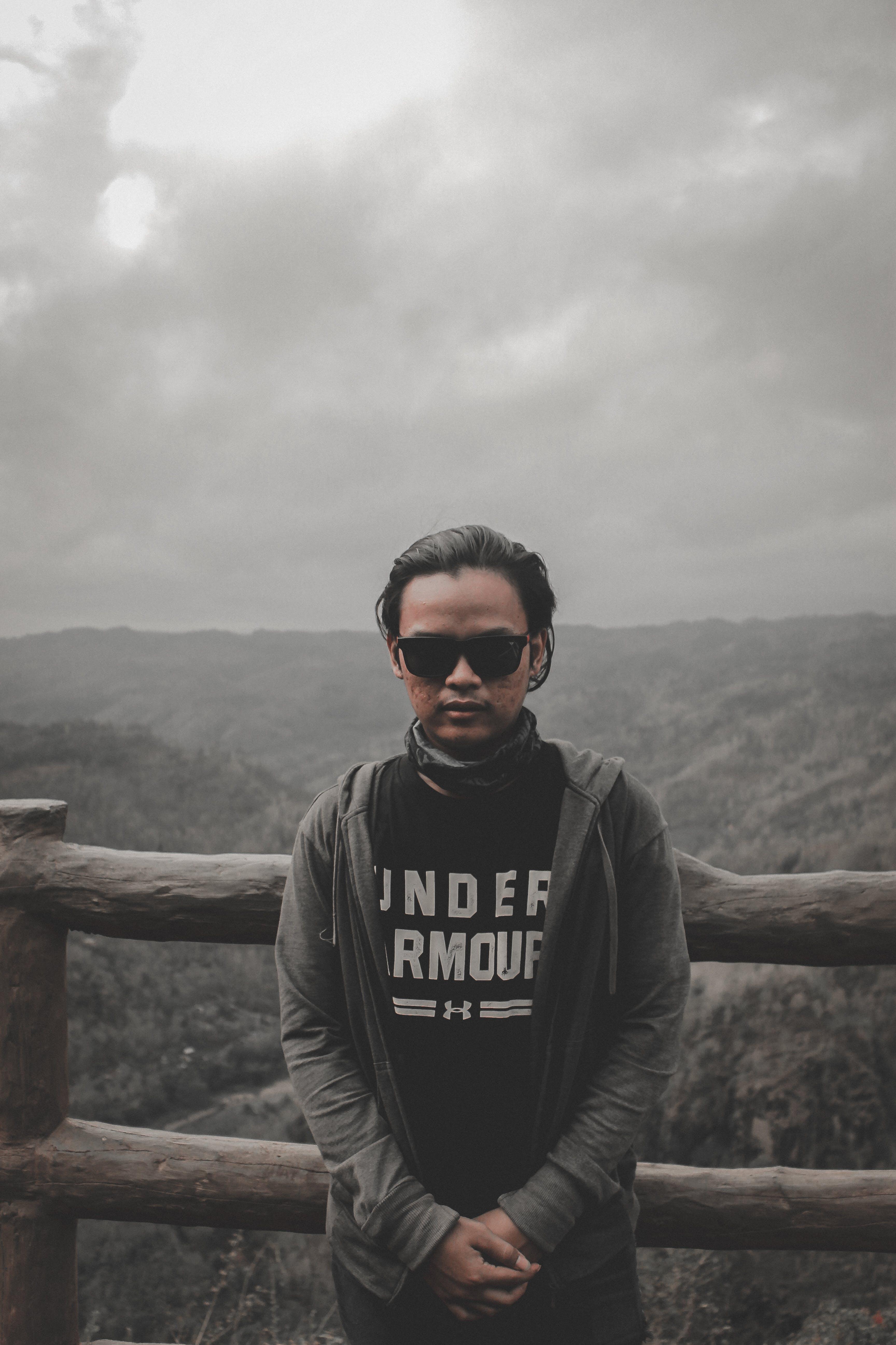 Man in Black Top and Grey Hoodie Jacket Standing Beside Brown Wooden