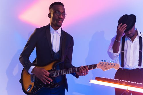 Man in Black Suit Playing an Electric Guitar