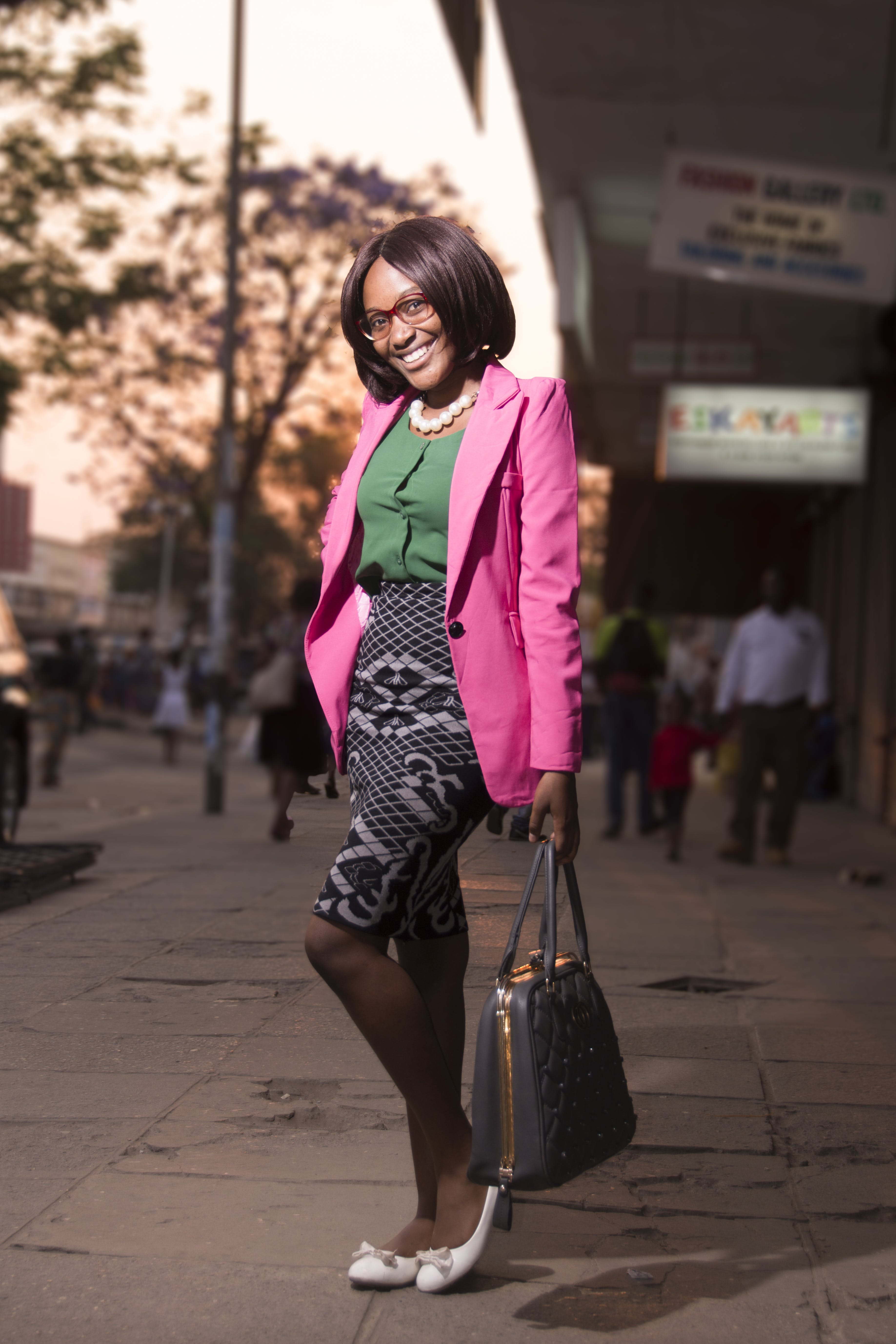 Woman in Pink Formal Coat and Green and Gray Dress With Black Hand Bag