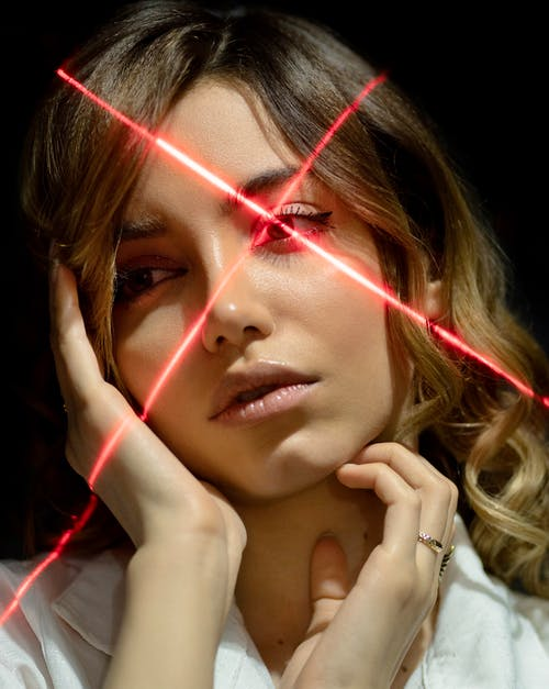 Young tender ethnic woman touching cheek and neck while looking away in laser beams on black background