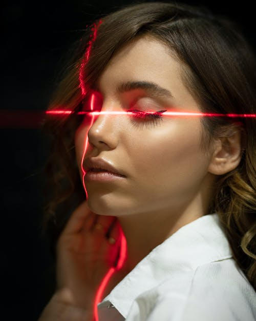 Tender ethnic model with closed eyes in laser beams
