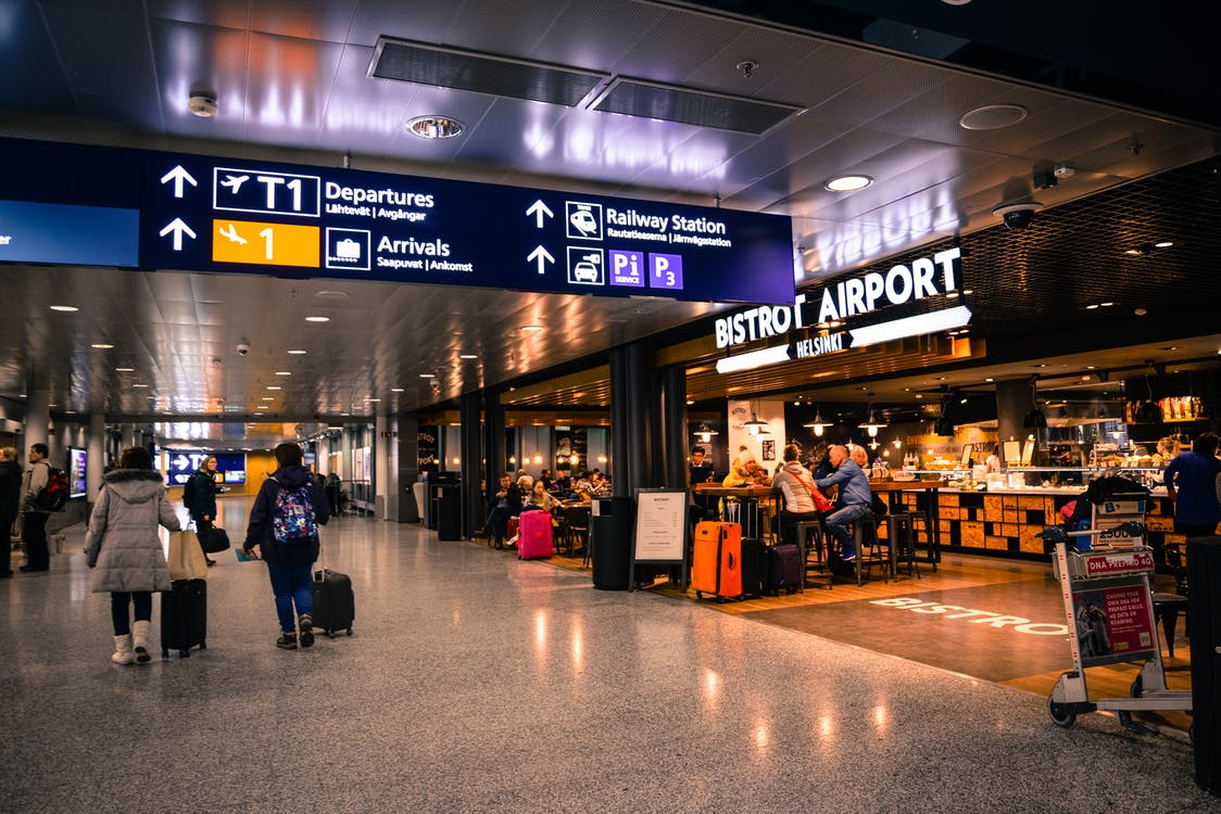 An airport's interior showcasing its wide hall and cafe inside - Booking Flights in Advance