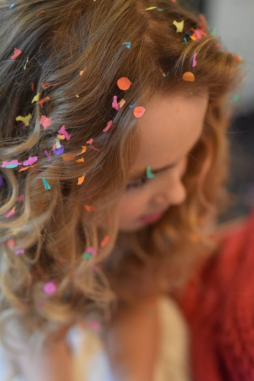 Shallow Focus Photography of Brown Haired Woman With Confetti on Hair
