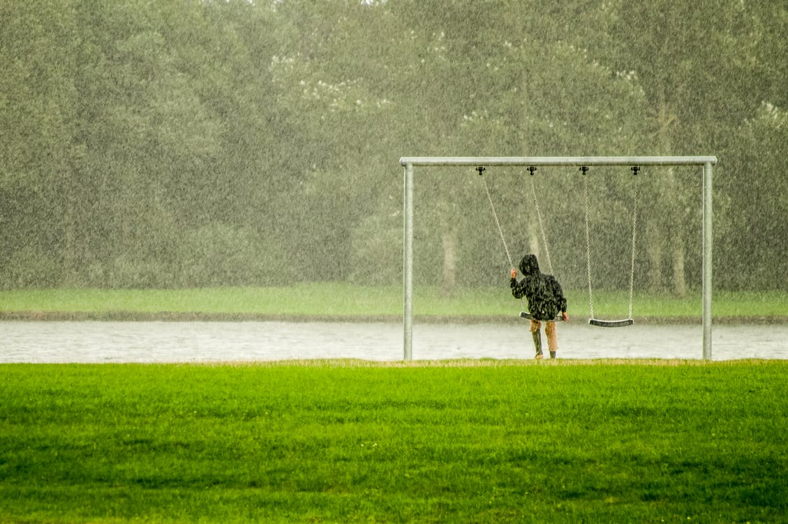 Person In Black Hoodie Riding Swing While Raining