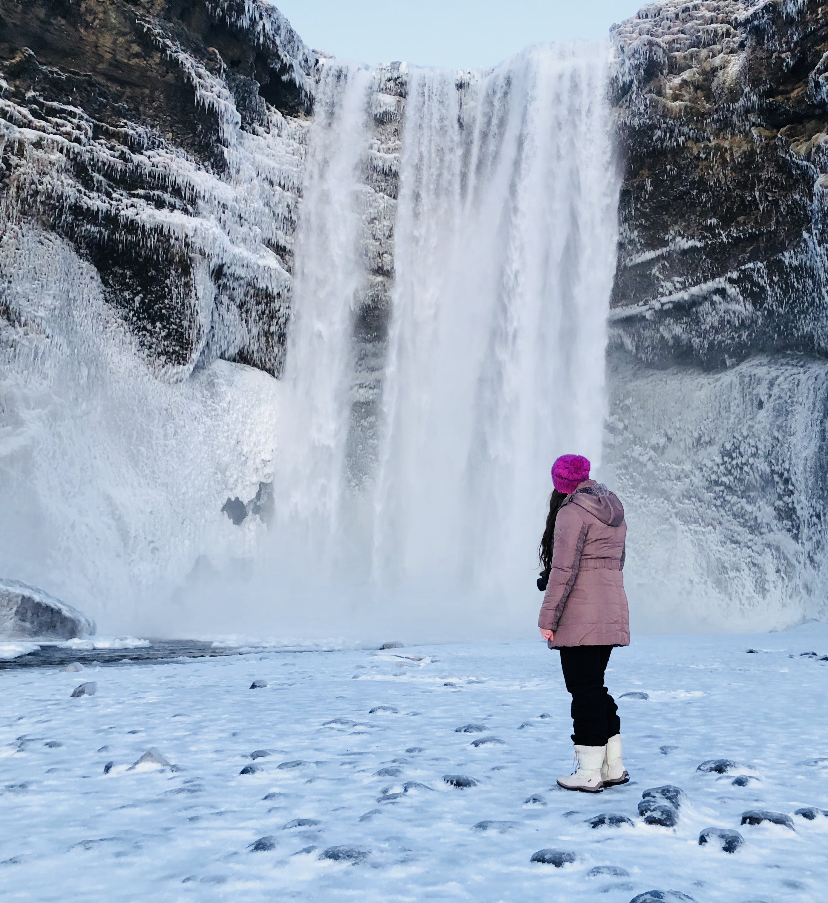 Woman Wearing Pink Snow Coat Standing on Field Full of Snow in Front of Frozen Waterfalls