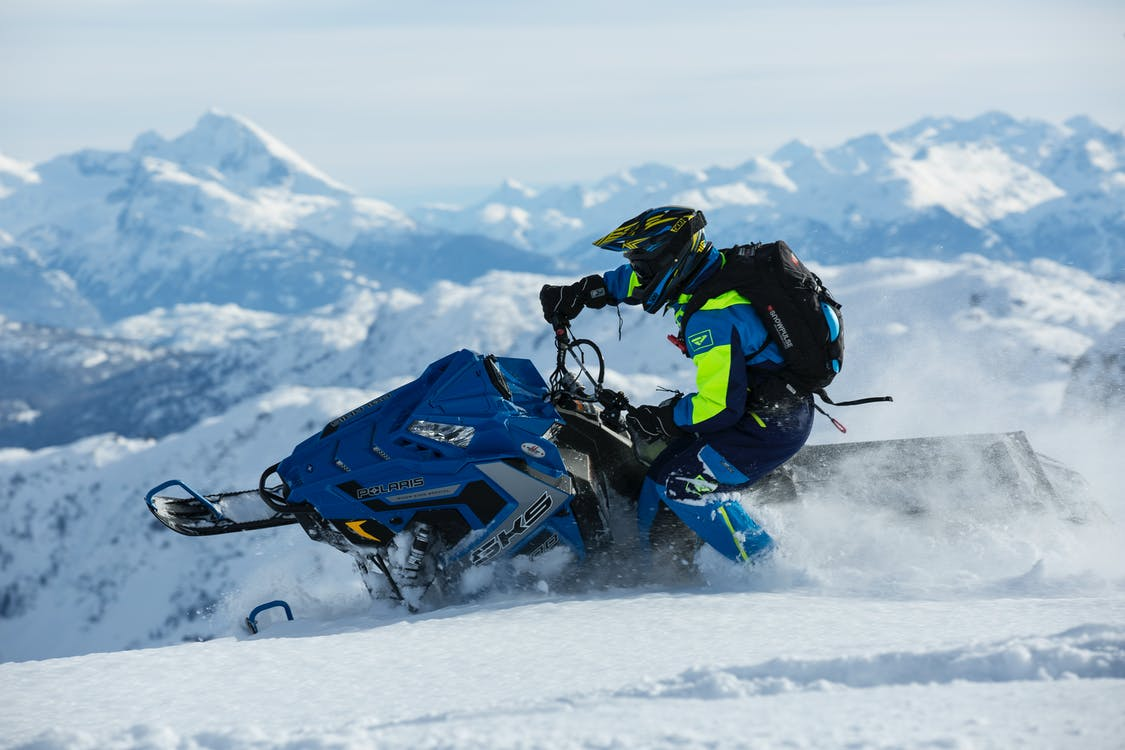 Man In Blue And Green Long-sleeved Suit Riding On Snowmobile