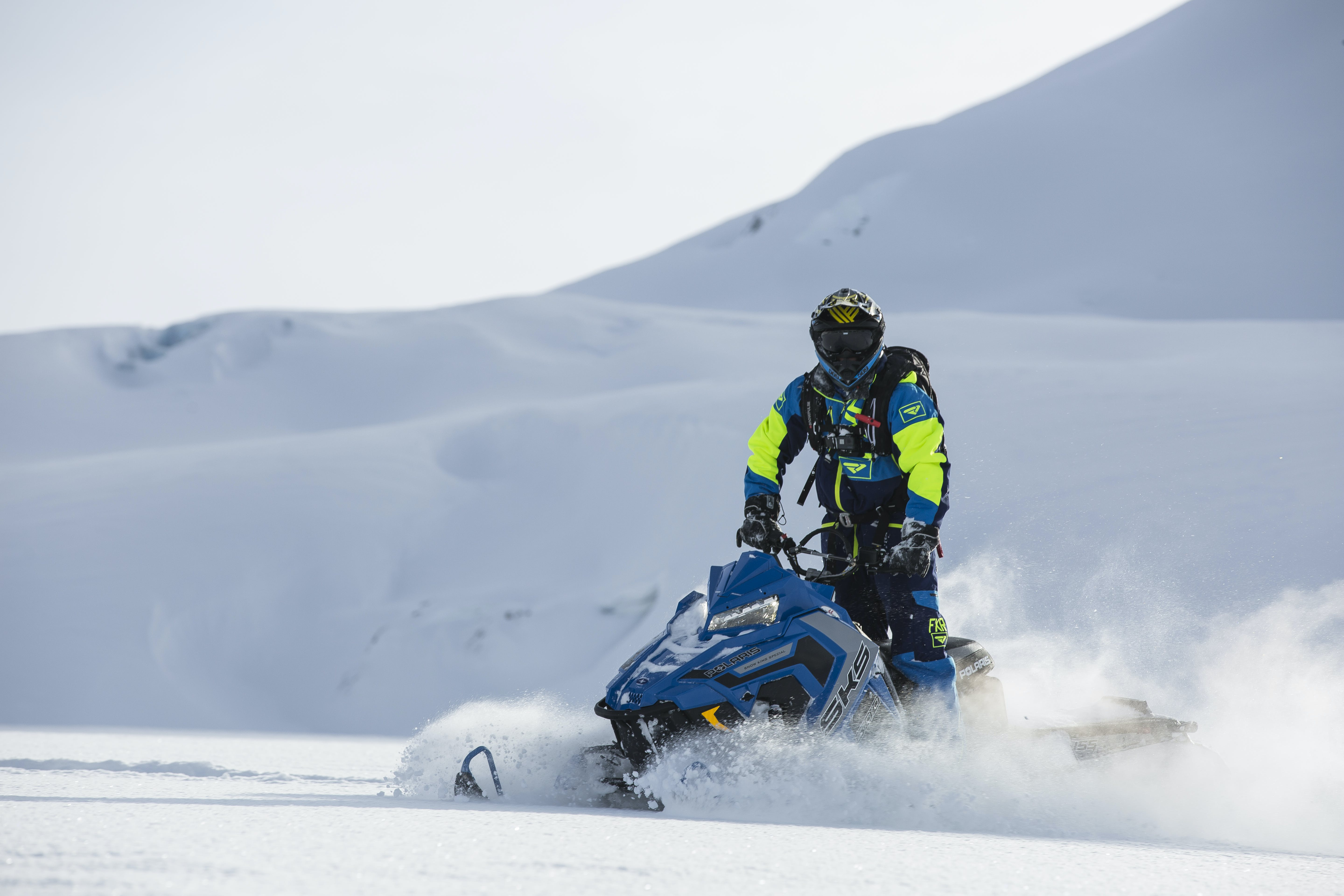 Person Rides on Blue Snowmobile at Daytime
