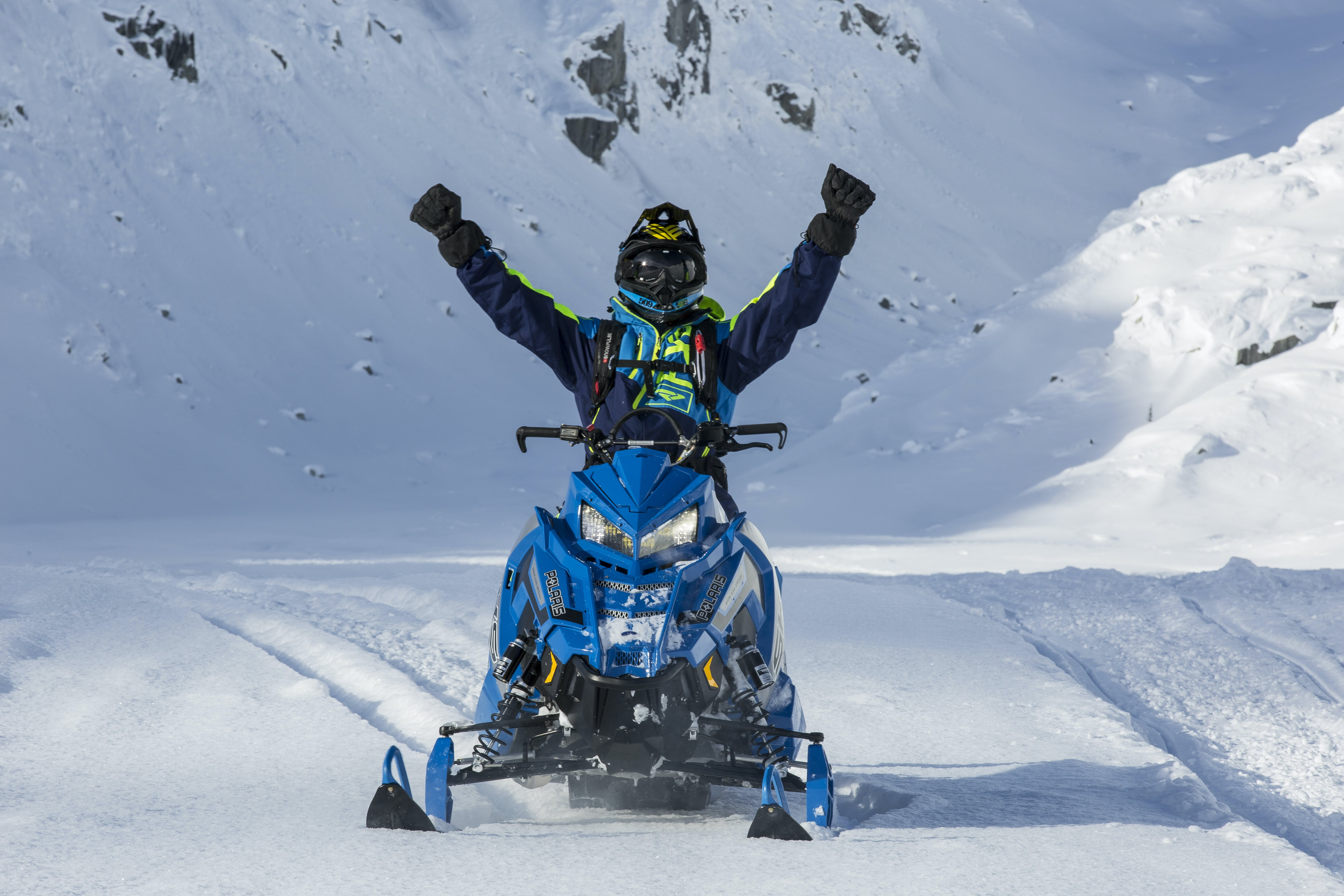 Person Riding Blue Snow Mobile