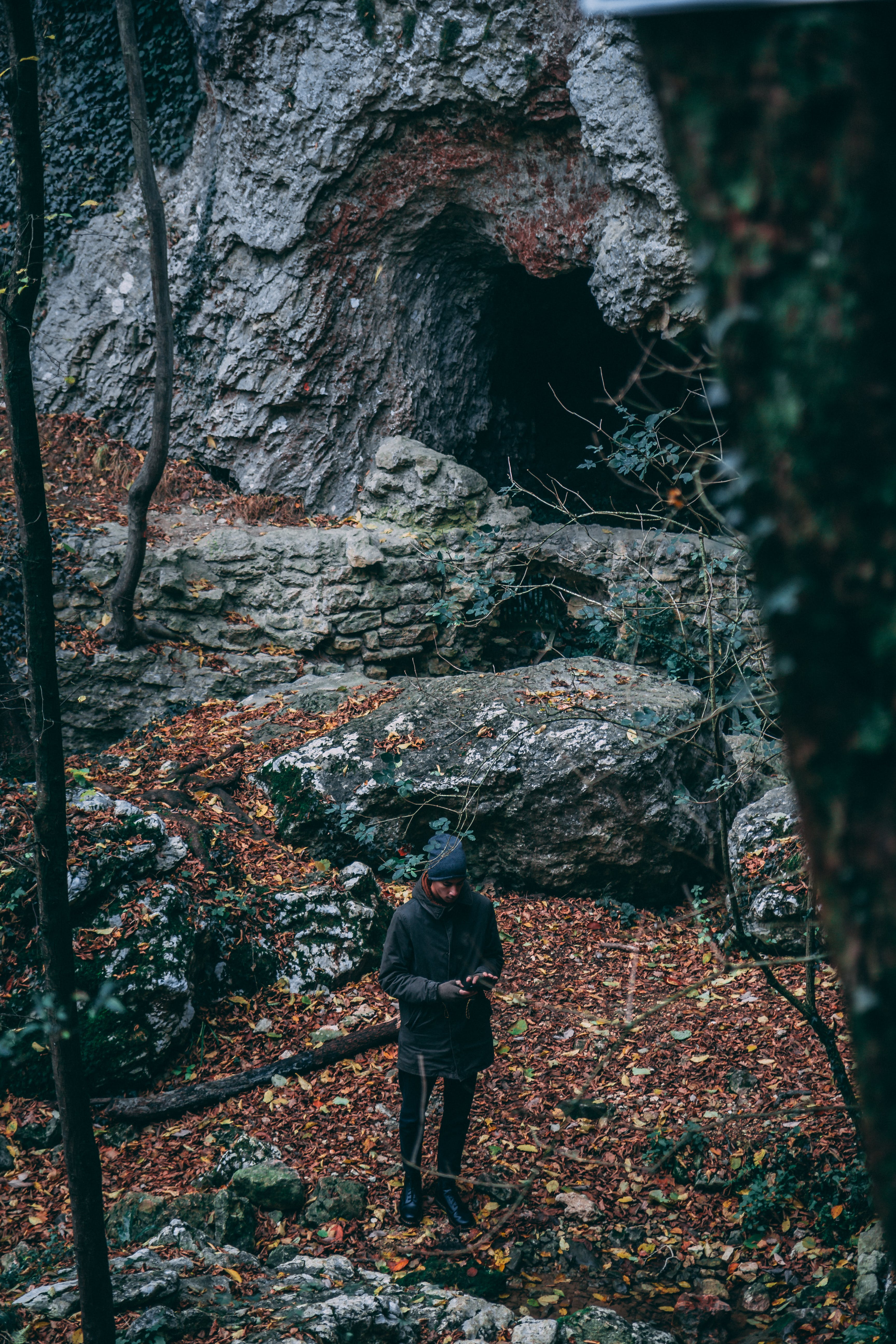 Man In Black Coat Standing Near Cave