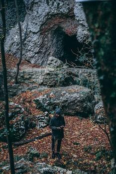 Man In Black Coat Standing Near Cave