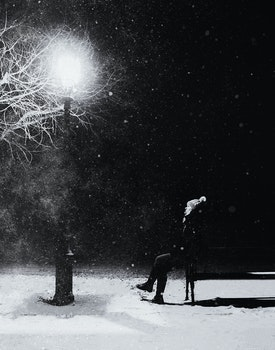 Grayscale Photography of Person With Knit Pompom Cap Sits in Front Turned on Light Post at Night