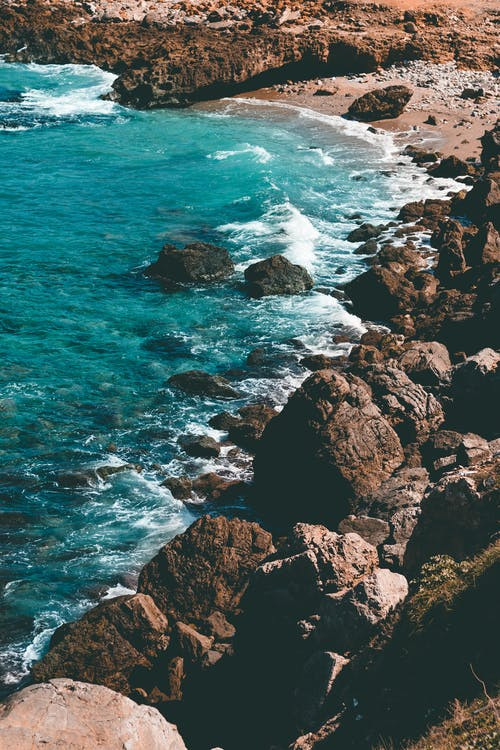 Brown Rocky Shore With Ocean Waves Crashing on Rocks