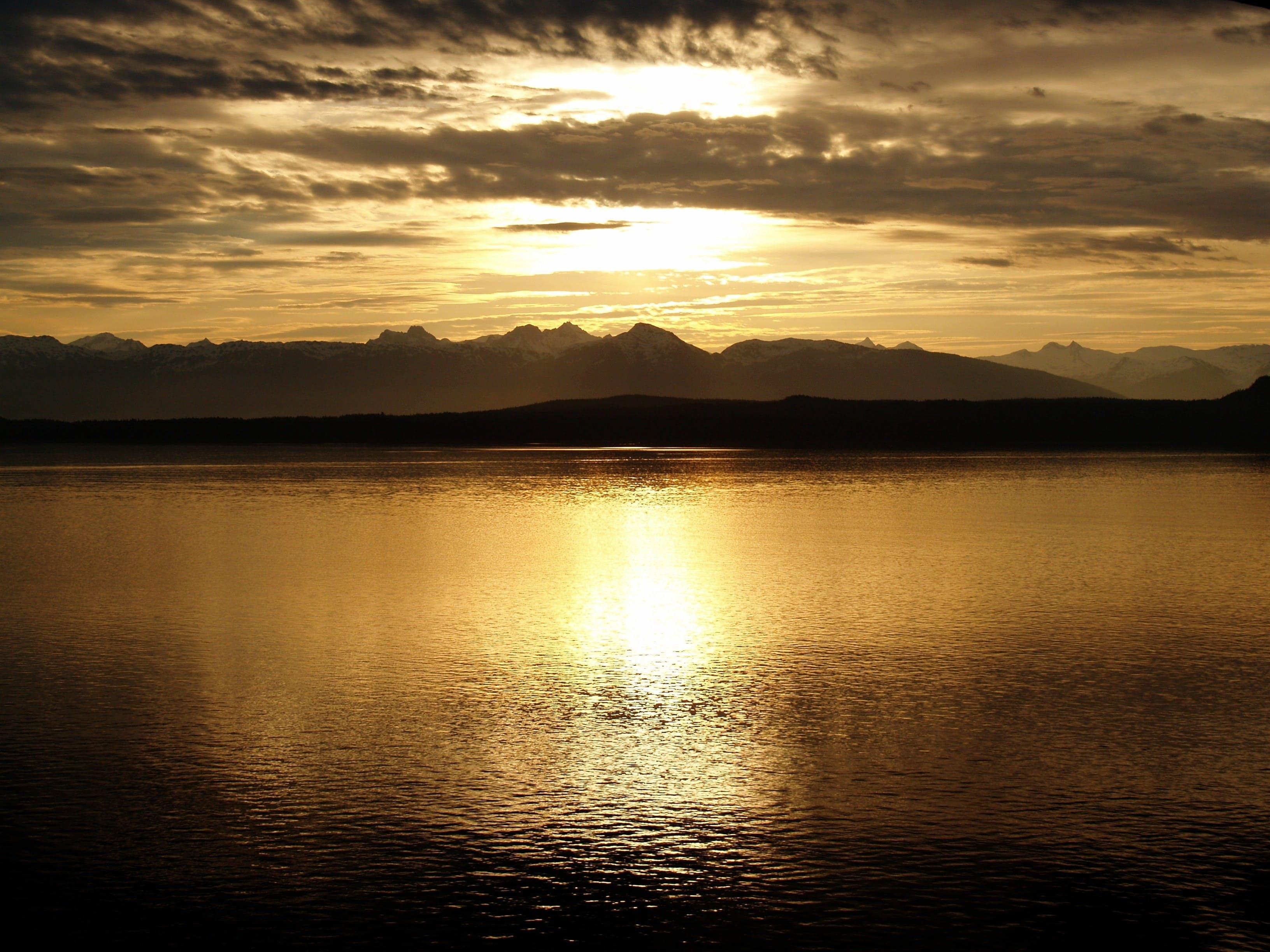 Calm Sea Near Mountain at Sunset