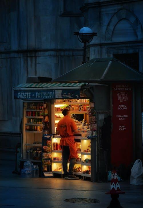 Man buying food in kiosk at night