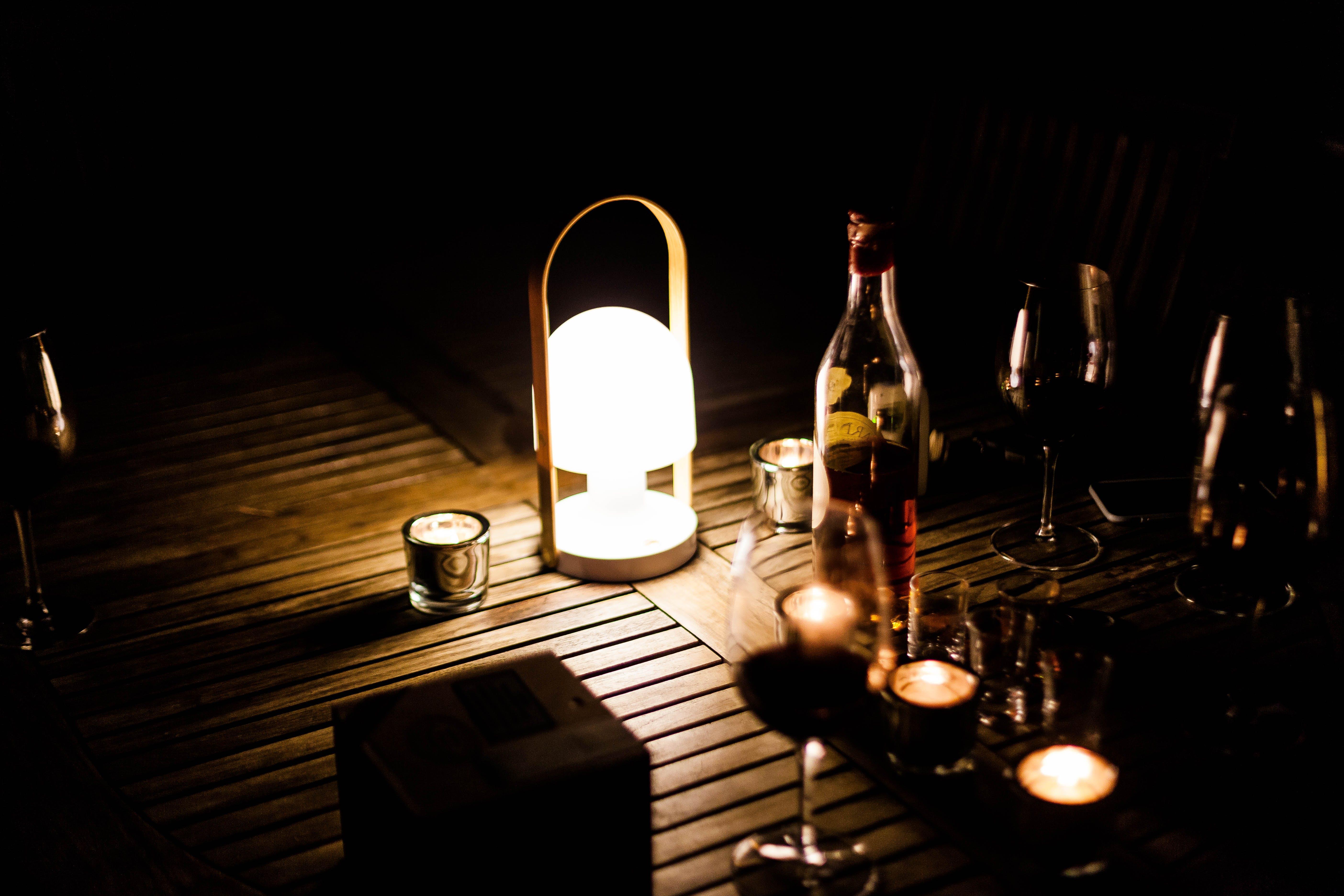 Turned on White Lamp Beside Wine Bottle