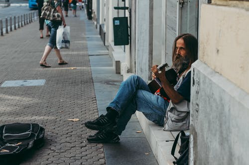 Man Playing Guitar While Sitting on Floor
