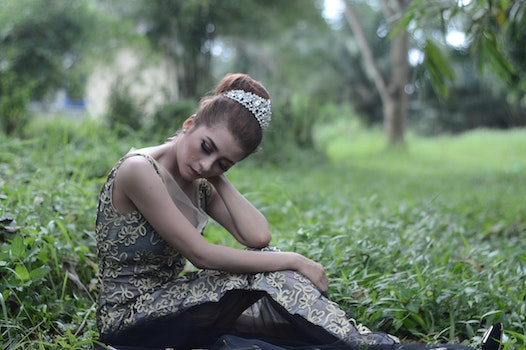 Woman Wearing Brown and White Sleeveless Floral Embroidered Dress Sitting on Green Grass Field