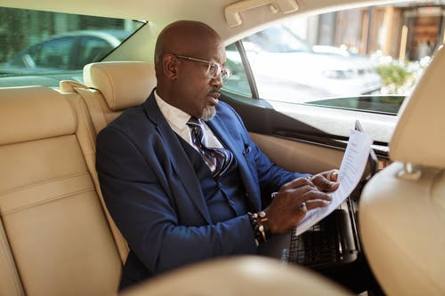 A Businessman Looking at His Documents Inside the Car