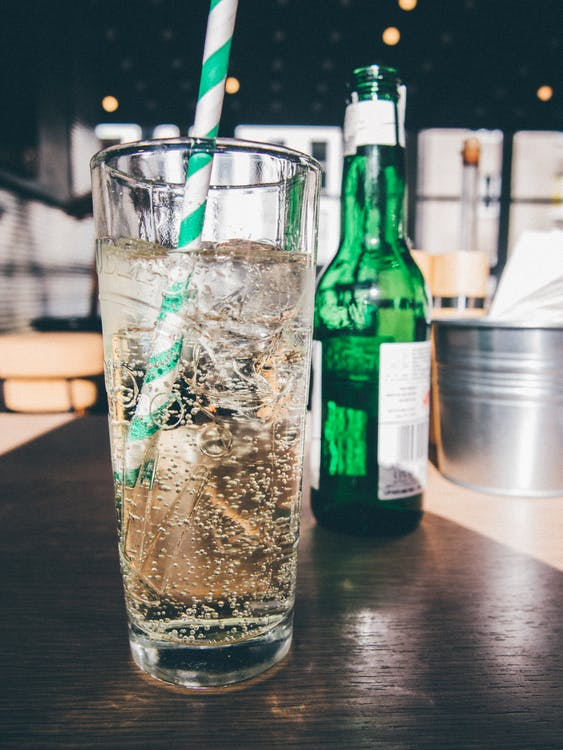 Clear Drinking Glass Filled With White Liquid and White Straw