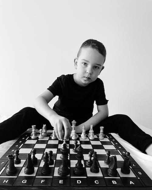 Boy in Black Crew Neck T-shirt Playing Chess