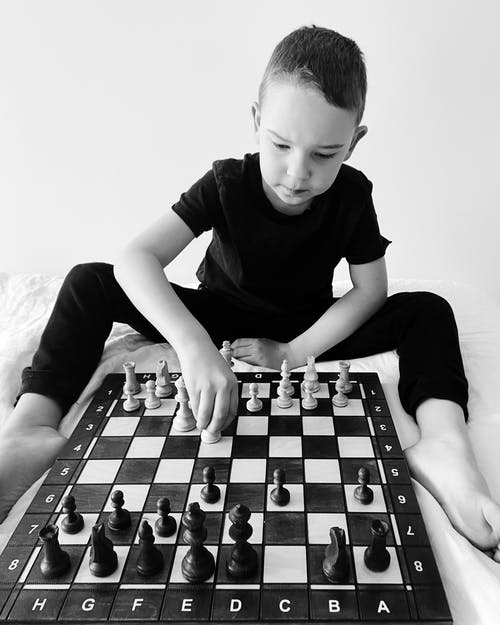 Boy Playing Chess on Table