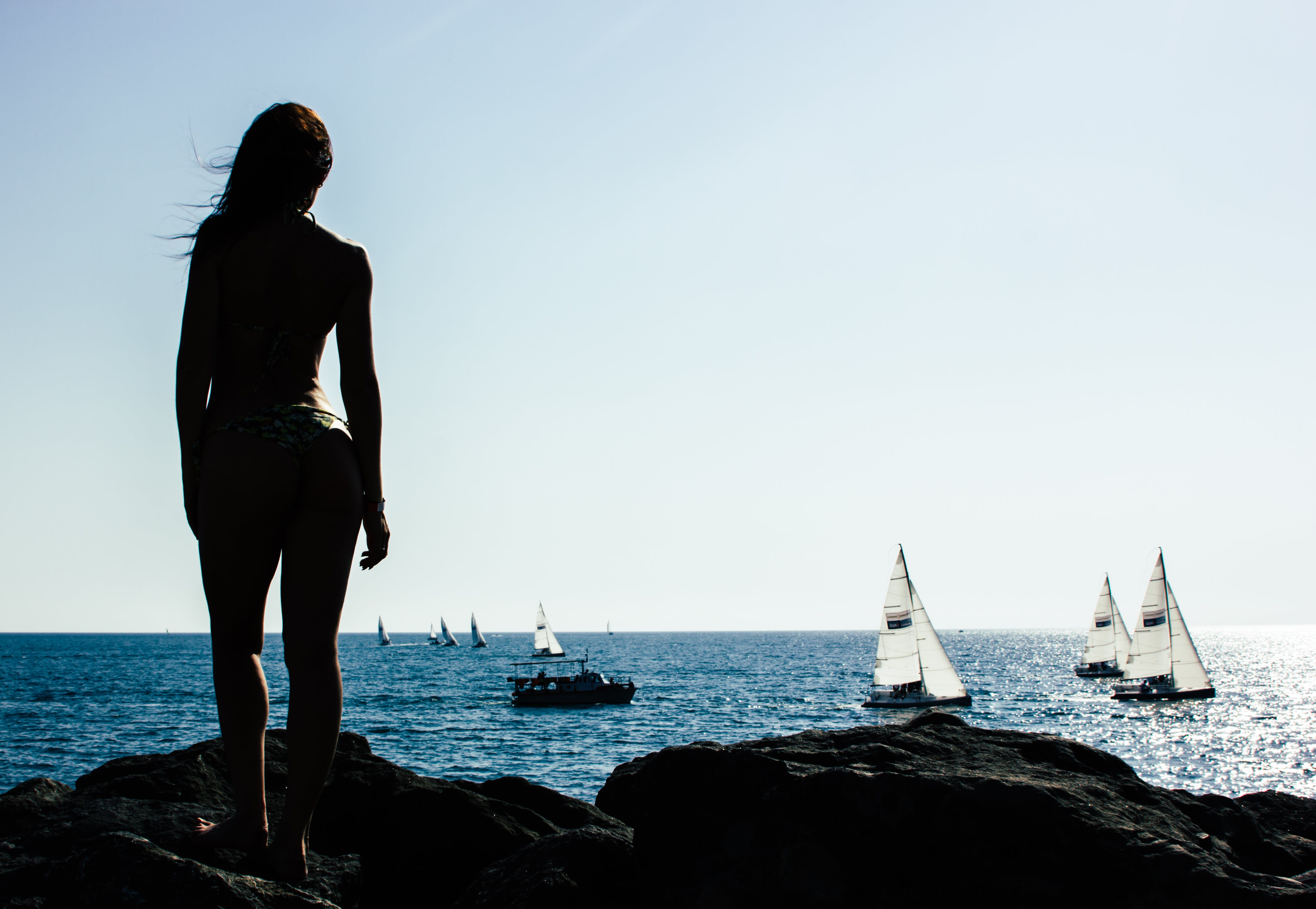 Woman Standing on Rock With Sailing Boats on Sea