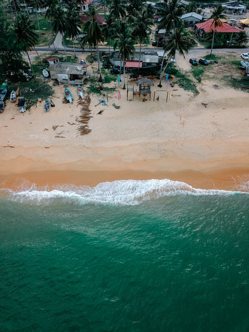 Amazing drone view of turquoise sea with white foamy waves rolling on sandy beach in tropical countryside with small houses land green palms