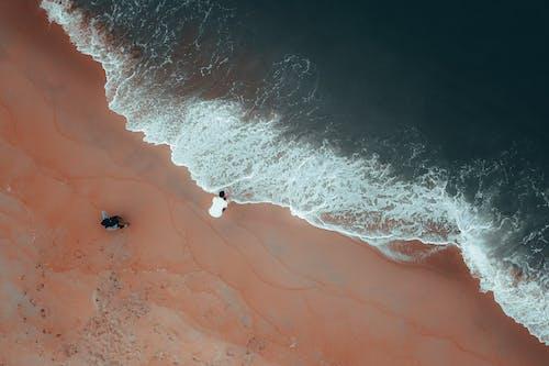 Anonymous travelers admiring powerful ocean from sandy coast
