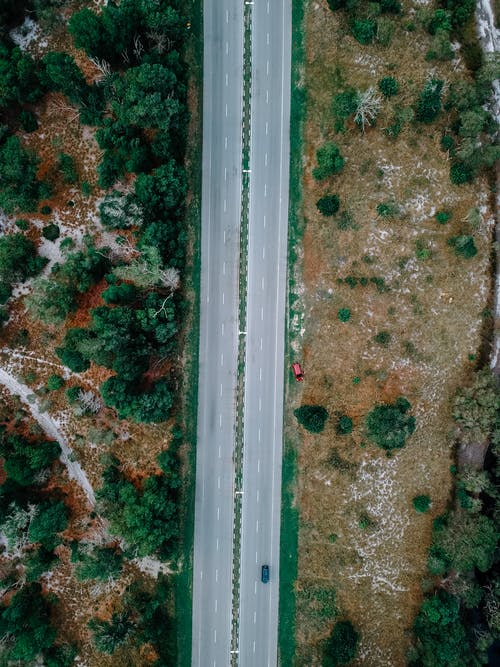 Aerial view of lonely car driving along asphalt road going through rural terrain with lush green trees and dry meadows