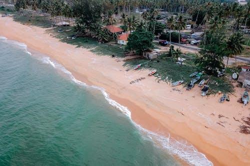 Sandy beach washing by wavy sea on sunny day in tropical village