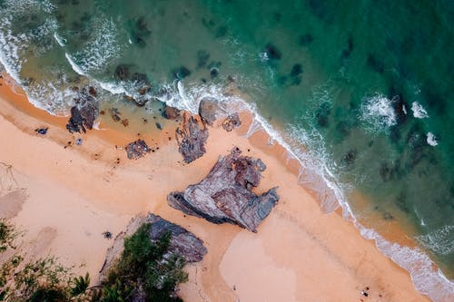 Aerial view of rocky cliffs on sandy shore of powerful foamy ocean on sunny day