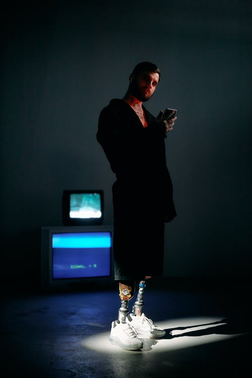 Photo of Man Standing on a Dark Room