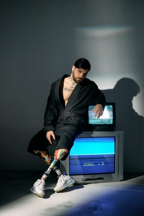 Photo of Man Sitting on a Television